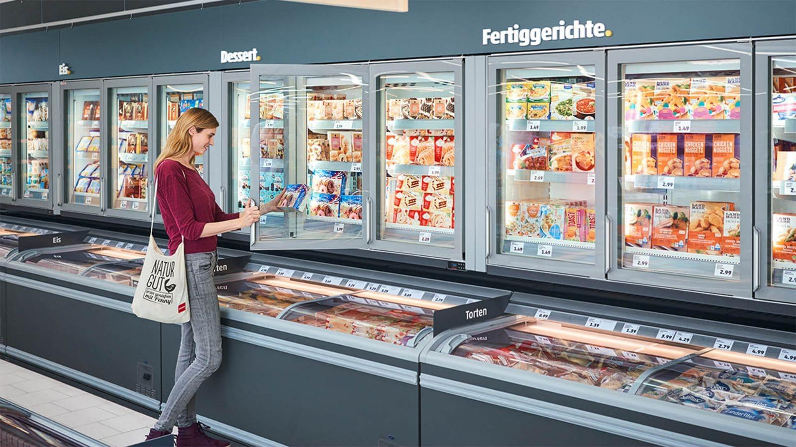 Frau in der übersichtlichen Tiefkühlabteilung des neuen Super-Discounts