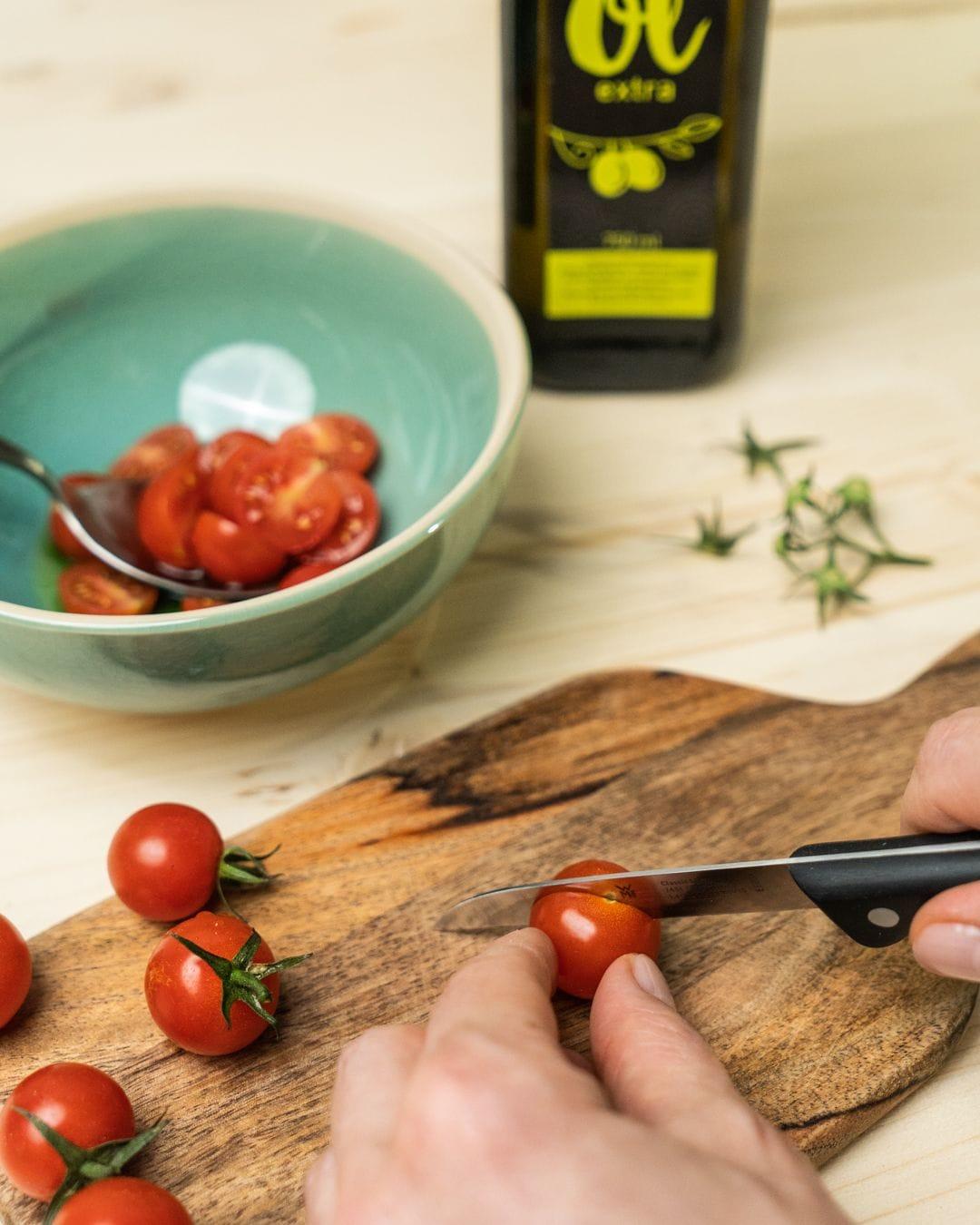 Auf diesem Bild siehst du wie Cocktail Tomaten geschnitten werden.