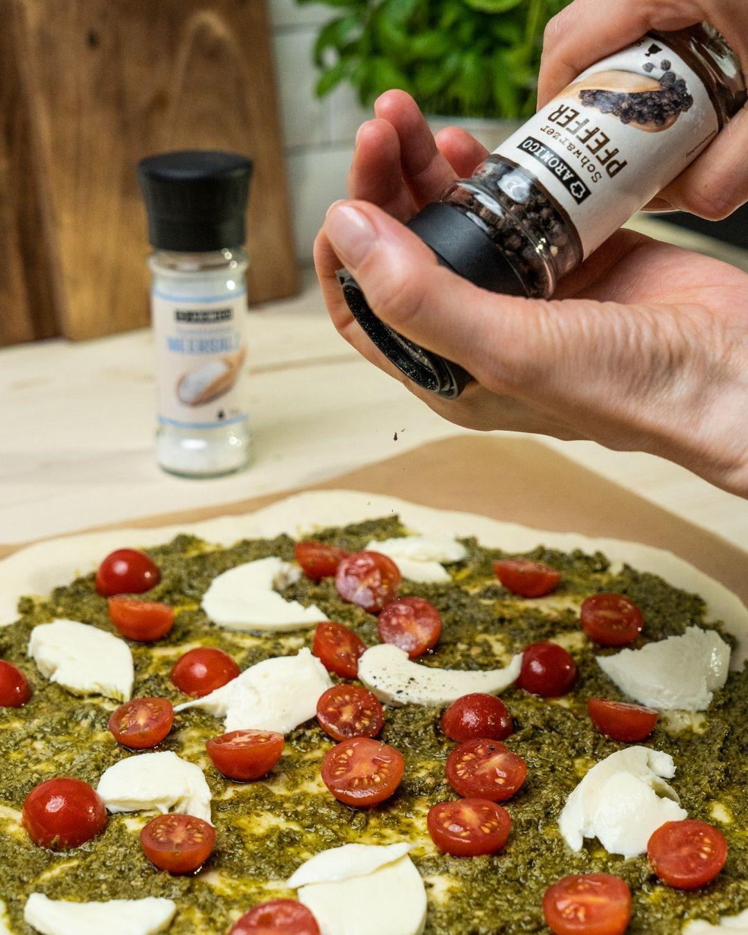 Auf diesem Bild siehst du wie die belegte Pizza belegt wird.