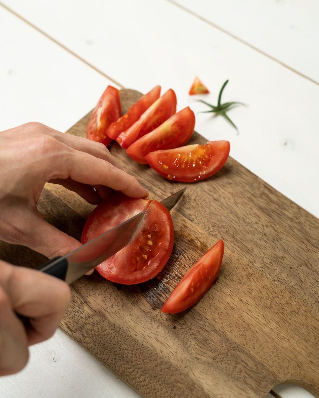 Auf diesem Bild siehst du wie eine Tomate geschnitten wird.