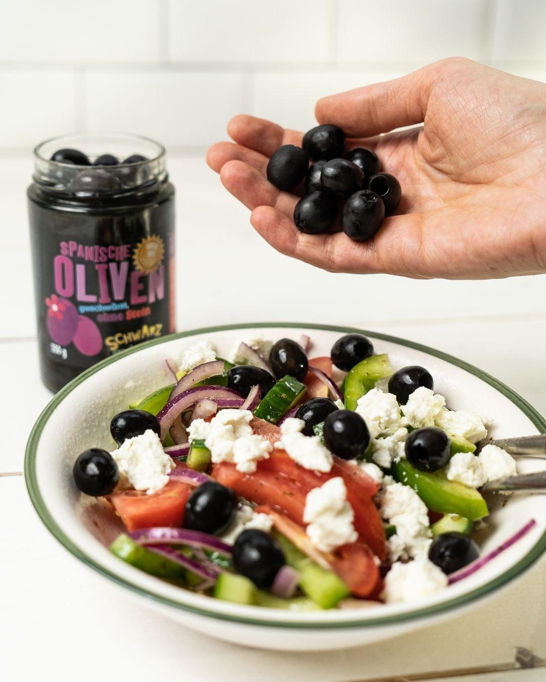 Auf diesem Bild siehst du wie Oliven in den Salat gegeben werden.
