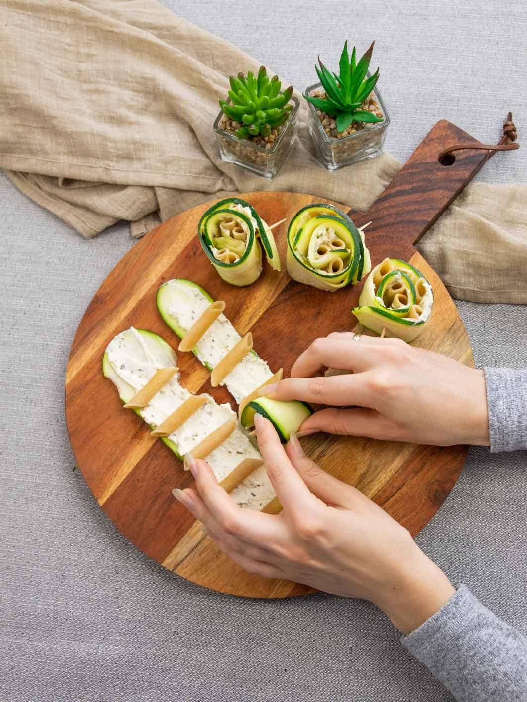 Auf diesem Bild siehst du wie die Nudeln in der Zucchini eingewickelt werden.